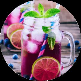 Herbata owocowa Malinowa Rapsodia, na zimno, w szklanym kubku z uchem. Do herbaty dodany lód, borówki, plastry limonki i mięta.